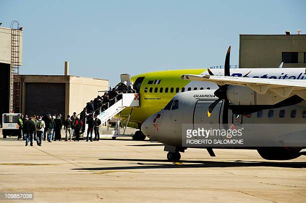 Immigrants who arrived on the island of Lampedusa in the last days board a plane for a temporary accomodation on February 15, 2011. A wave of...