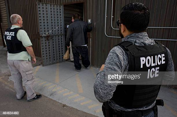 US Immigration and Customs Enforcement agents look on as an undocumented man is received by a Mexican immigration agent at a removal gate of the...
