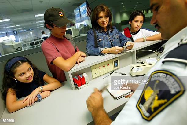 S Immigration Inspector Eligio Perez checks the passports of a family July 2 2002 at Miami International Airport in Miami Forida Inspectors are using...