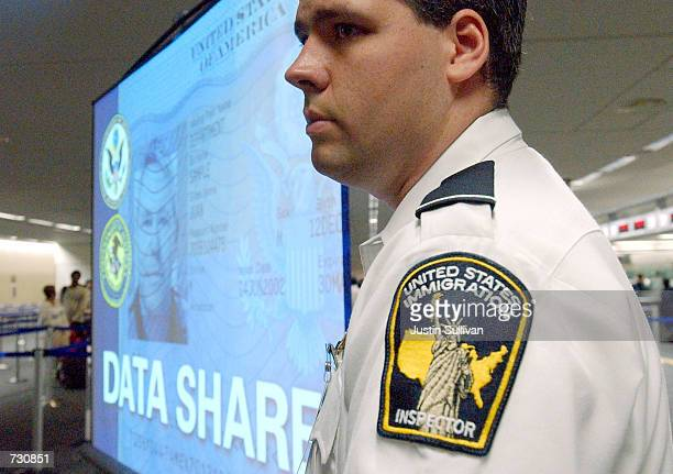 S immigration inspector Jimmy Mollison stands next to a screen displaying information on a new technological service known as DataShare at San...