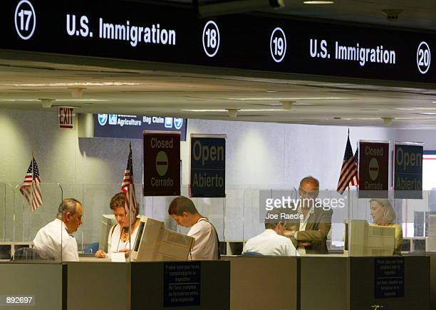 S Immigration inspectors check passports July 2 2002 at Miami International Airport in Miami Forida Inspectors are using the new multiagency...