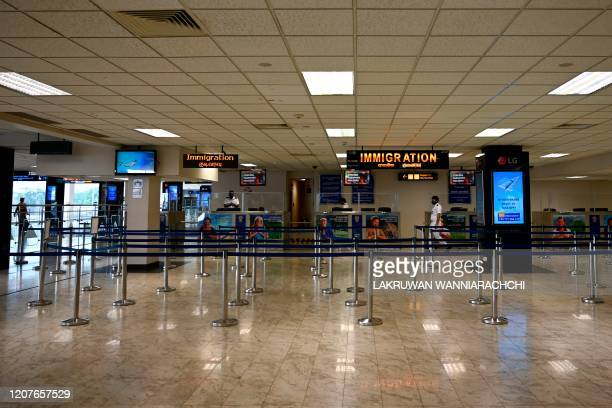 Immigration officers sit behind their counters at the arrival terminal of the Bandaranaike International airport in Katunayake on March 19 following...