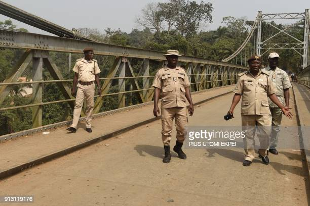 Immigration officers walk on a suspension bridge built in 1948 that connects Nigeria with Cameroon at Mfum border station in Cross Rivers State...