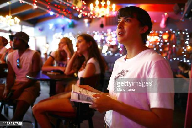 Immigration rights activist Angel Ulloa views the debate broadcast during a watch party for the first night of the Democratic presidential debate on...