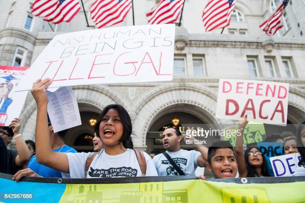 Immigration rights demonstrators hold signs in front of the Trump International Hotel in Washington to oppose President Trump's decision to end the...
