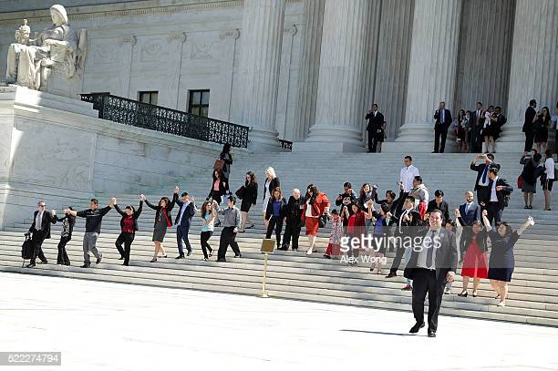Immigration supporters hold up their hands and walk down the steps of the US Supreme Court April 18 2016 in Washington DC The Supreme Court heard...