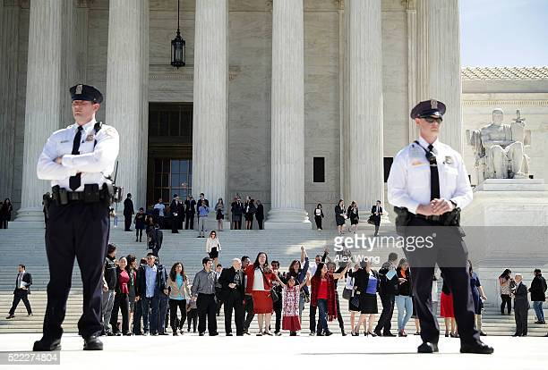 Immigration supporters hold up their hands as they come out of the US Supreme Court April 18 2016 in Washington DC The Supreme Court heard oral...