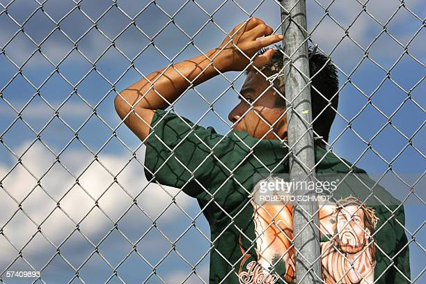 """Immokalee, UNITED STATES: TO GO WITH AFP STORY """"EEUU-MIGRACION-HISPANOS"""" An immigrant farm worker looks from behind a fence as he listens to a leader..."""