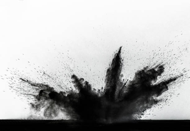 Impact and explosion of black dust and smoke particles on a white background.