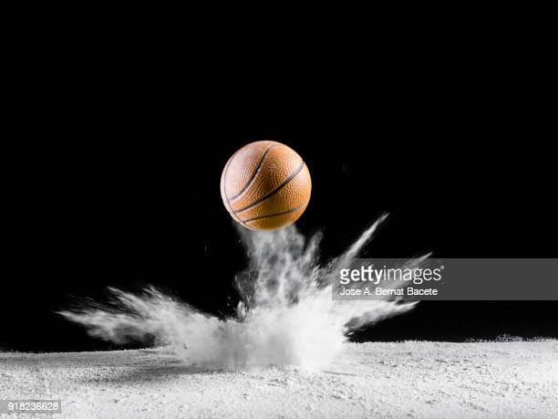 Impact and rebound of a ball of basketball on a surface of land and powder on a black background
