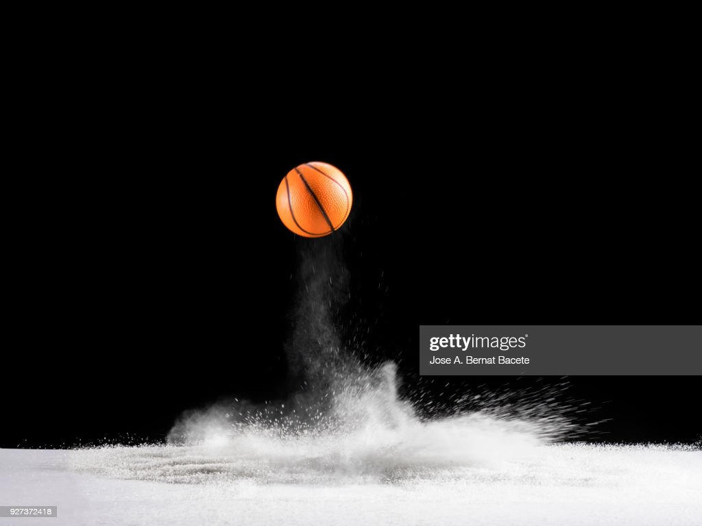 Impact and rebound of a ball of basketball on a surface of land and powder on a black background : Stock Photo