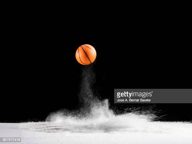impact and rebound of a ball of basketball on a surface of land and powder on a black background - bouncing stock pictures, royalty-free photos & images