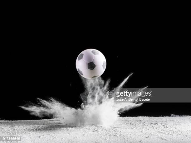 Impact and rebound of a ball of soccer on a surface of land and powder on a black background