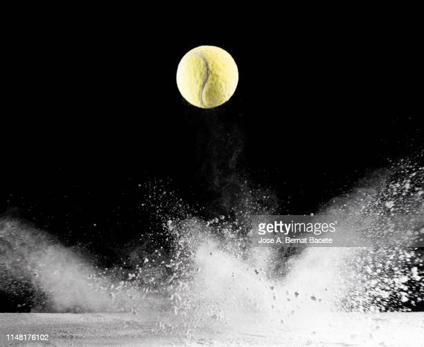 impact and rebound of a ball of tennis on a surface of land and powder on a black background - dribbling stock pictures, royalty-free photos & images