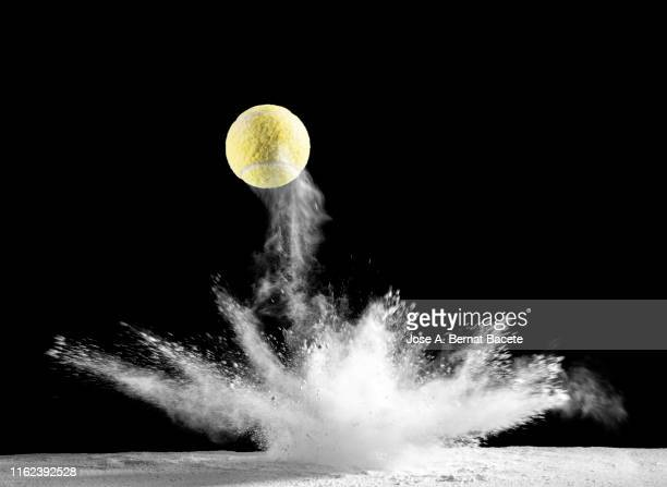 impact and rebound of a ball of tennis on a surface of land and powder on a black background - studio shot stockfoto's en -beelden