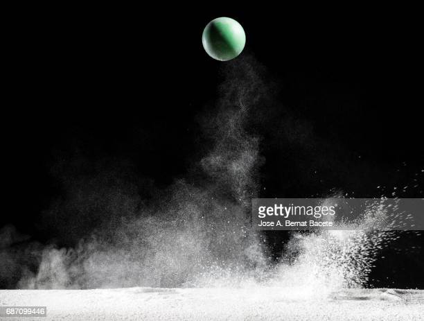 Impact and rebound of a ball   on a surface of land and powder on a black background