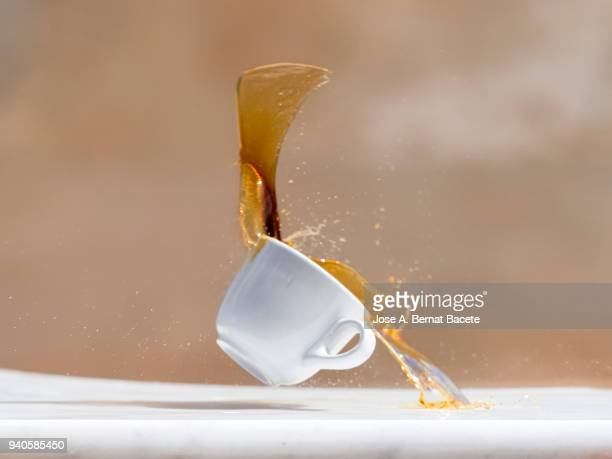 impact of a coffee cup that falls down on the soil. - exploding glass stock photos and pictures