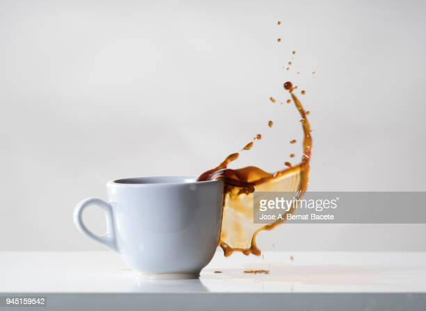 impact of a coffee cup that falls down on the table. - adversidade imagens e fotografias de stock