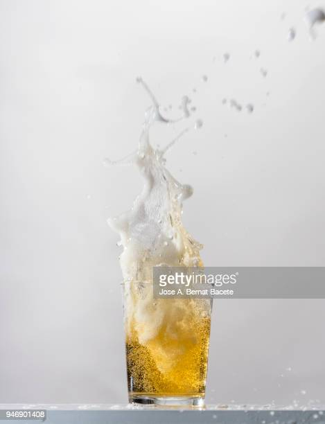 impact of a glass with beer that falls down on the table. - exploding glass stock photos and pictures