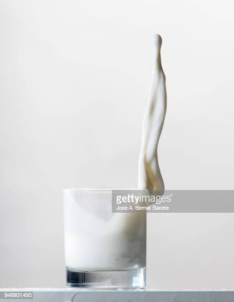 impact of a glass with milk that falls down on the table. - tropfen aufprall stock-fotos und bilder