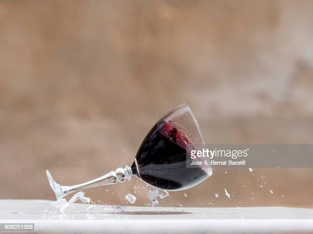 impact of a wine glass of red wine that falls down on the soil. - alcoholismo fotografías e imágenes de stock