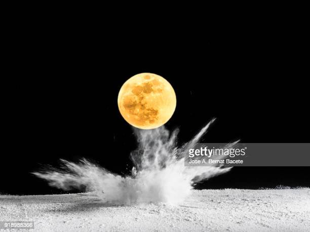 Impact of full moon (Super moon) on the soil, producing an explosion and a crater of powder on a black background. Spain