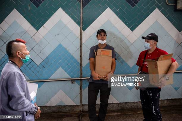 ImpactHK founder and CEO Jeff Rotmeyer and others carry supplies of face masks hand sanitisers food and drinks to hand out to the homeless and people...