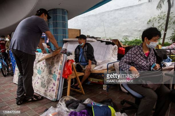 ImpactHK founder and CEO Jeff Rotmeyer speaks to a homeless man after handing out supplies of face masks hand sanitiser food and drinks in Hong Kong...