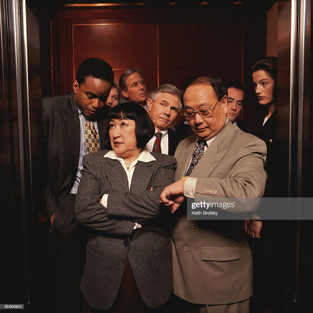 Impatient Businesspeople in a Crowded Elevator : Stock Photo