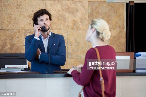 Impatient customer waiting while hotel receptionist talks on phone