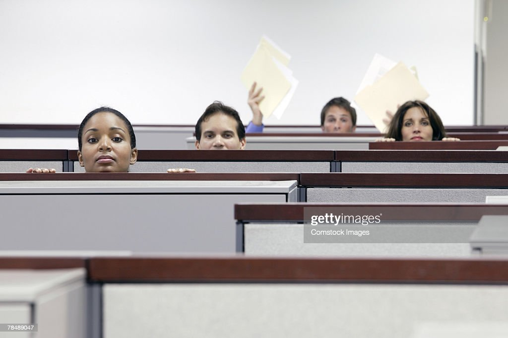 Impatient office workers looking over cubicle walls : Stock Photo