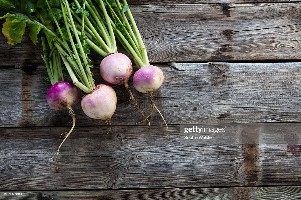 imperfect organic turnips, fresh green tops on authentic wood background : Stock Photo