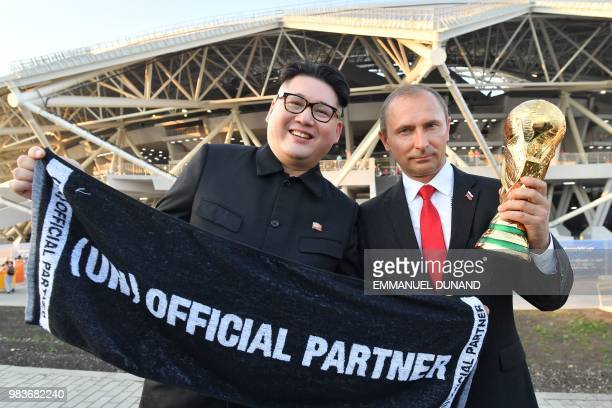 Impersonators of Russian President Vladimir Putin and North Korean leader Kim Jong Un pose with a replica of the World Cup trophy at the end of the...