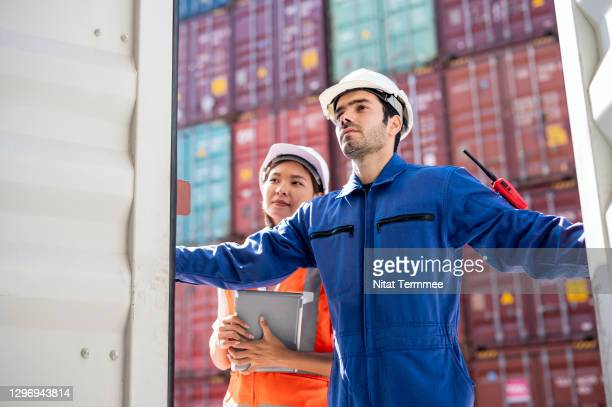 import, export and freight forwarder business concept.  male dock worker and female customs is working at shipping yard while opening the container to declare the product inside. - harbour stock pictures, royalty-free photos & images