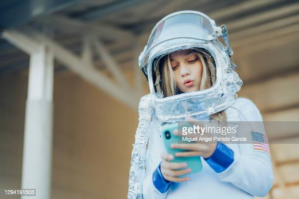 important call. young serious astronaut is holding a helmet and a modern mobile phone while looking at the device screen with concentration. isolated with copy space on the left side. - 宇宙ミッション ストックフォトと画像