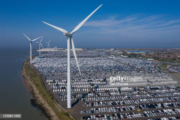Imported automobiles sit at the docks in the shadow of wind turbines on April 23 2020 in Sheerness United Kingdom New car sales are down a reported...