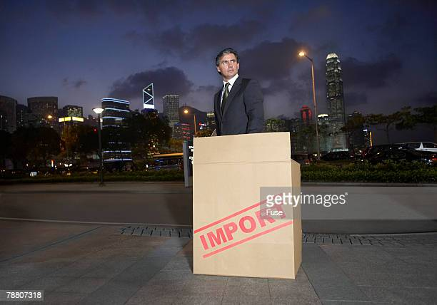 Imported Businessman in Carboard Box on Sidewalk