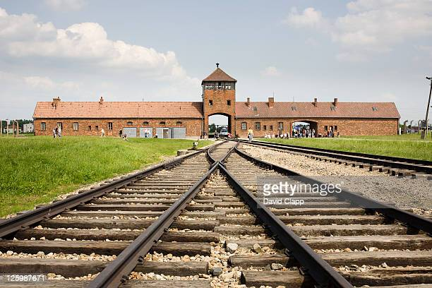imposing entrance gates and railway lines at birkenau, auschwitz concentration camp in poland - birkenau stock pictures, royalty-free photos & images
