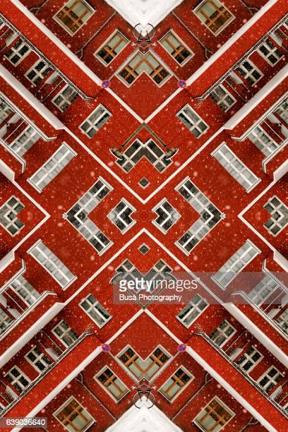 Impossible architectures: digital manipulation of red facade of residential house in  winter on a snowy day in Berlin, Germany