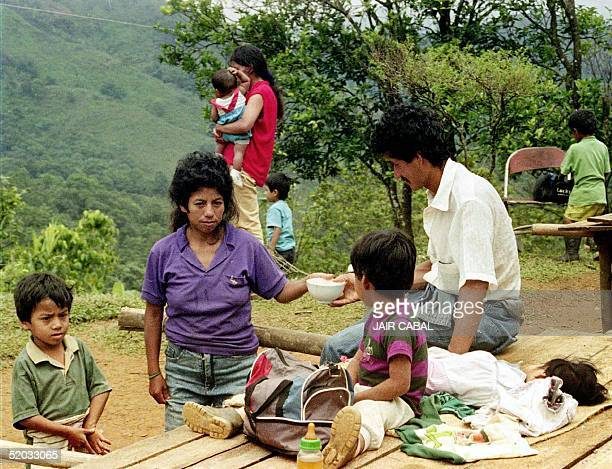 Impoverished refugees share a meal 11 June in a refugee camp 50 km south of Cali Colombia Some 20 families have been displaced by fighing between...