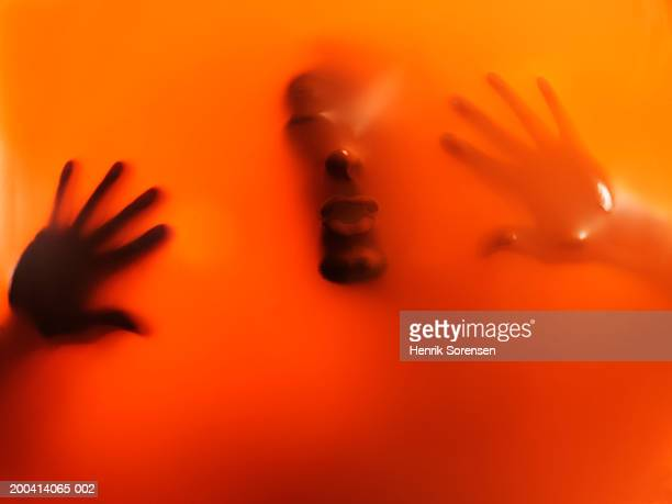 Impression of man's face and hands through orange rubber, close-up