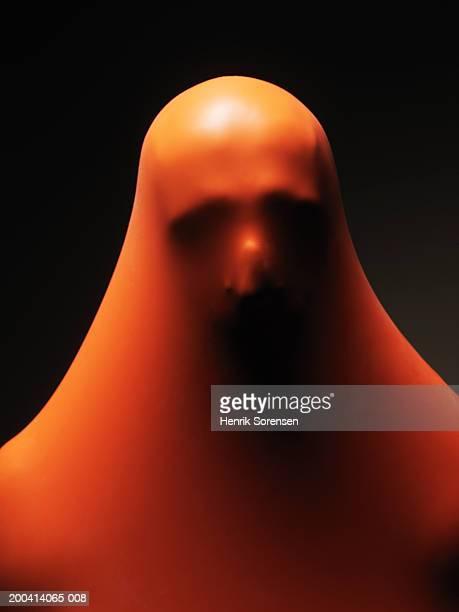 Impression of man's head through orange rubber, close-up