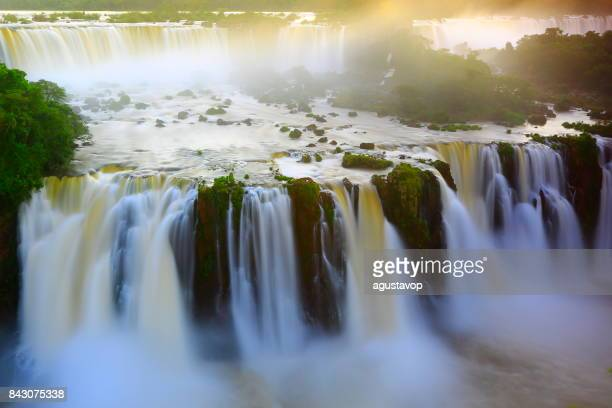 impressive iguacu falls landscape, blurred motion from long exposure at dramatic sunset - idyllic devil's throat - international border of brazilian foz do iguacu, parana, argentina puerto iguazu, misiones and paraguay - south america - brasil stock pictures, royalty-free photos & images