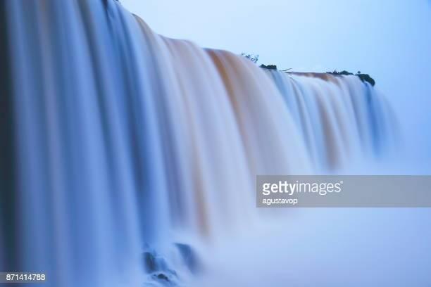 Impressive Iguacu falls landscape, blurred motion from long exposure at peaceful dawn - Idyllic Devil's Throat - international border of Brazilian Foz do Iguacu, Parana, Argentina Puerto Iguazu, Misiones and Paraguay - South America