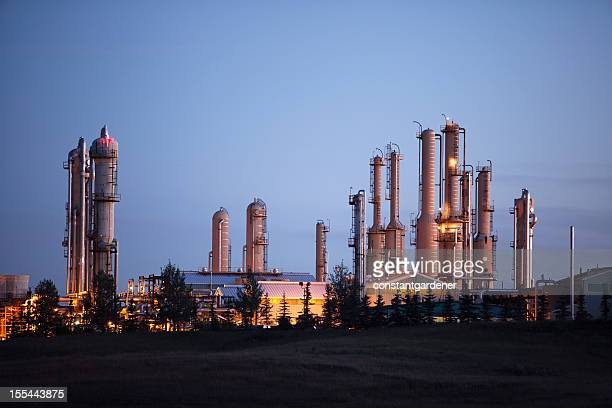 impressive looking gas plant with lights at dusk - gas refinery stock photos and pictures