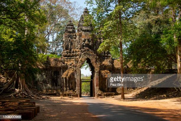 impressive old stone entrance with stone sculpture on top of the gate at angkor thom. angkor thom, angkor wat, cambodia, south east asia. - angkor wat stock pictures, royalty-free photos & images