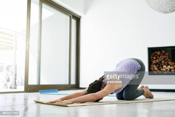 improving her flexibility through yoga - childs pose stock photos and pictures