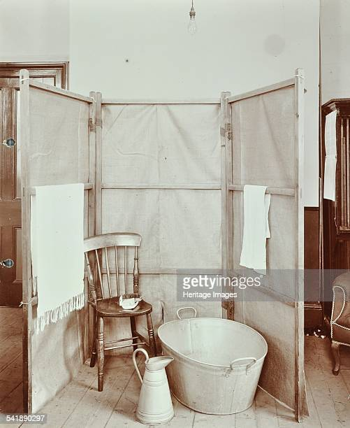 Improvised bathroom, Shoreditch Technical Institute, London, 1907. Consisting of a tin bath and jug behind a screen. Artist: unknown.