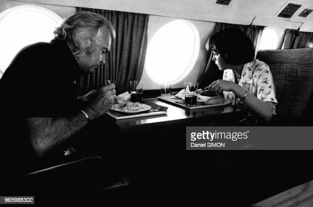 L'imprésarion Johnny Stark et la chanteuse Mireille Mathieu regardant par le hublot devant un plateau repas dans l'avion pour Nice afin d'assister au...
