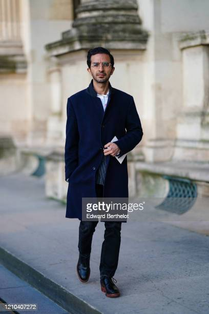 Imran Amed, founder and CEO of Business of Fashion, wears glasses, a navy blue long coat, blue denim pants, black leather shoes, outside Vuitton,...